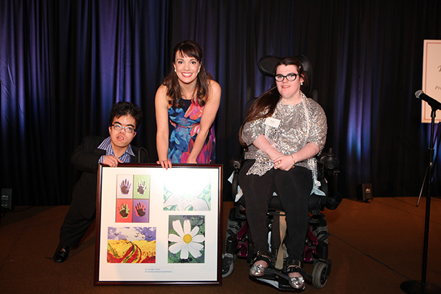 Broadway's Kara Lindsay while holding a piece of art work with two students from the Henry Viscardi School at the Reach for a Star Luncheon.