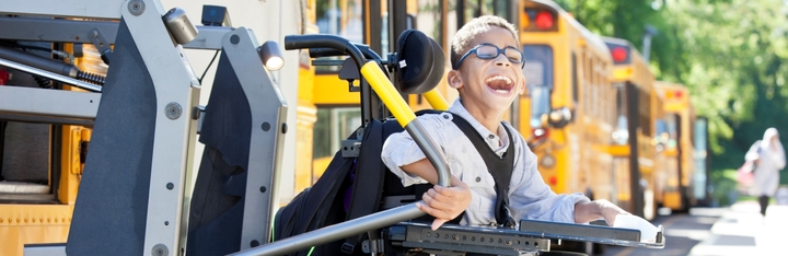A young boy in a wheelchair smiling as he gets off the school bus